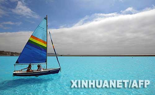 图片:游客乘小船漂游在世界上最大的游泳池内
