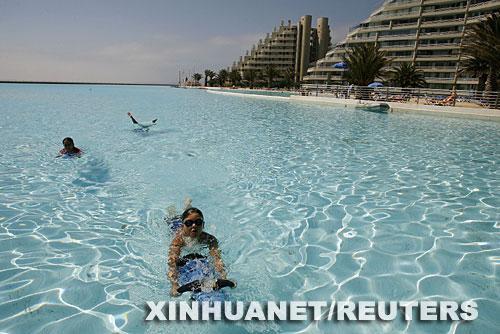 图片:游客们在智利海滨城市阿尔加罗沃的一座游泳池内戏水